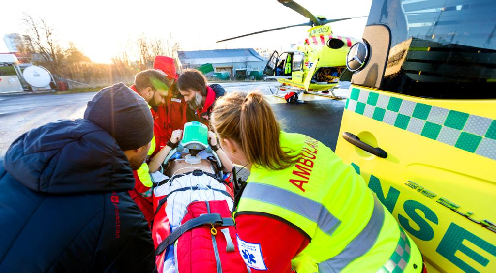 Pasient lastes inn i helikopter. Foto.