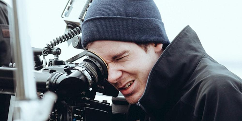 Mann filmer med kamera. Foto