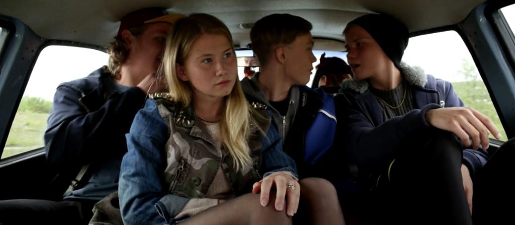 Tre ungdommer i baksetet av en bil, utsnitt fra scene i kortfilmen Hilbes biigá. Foto.