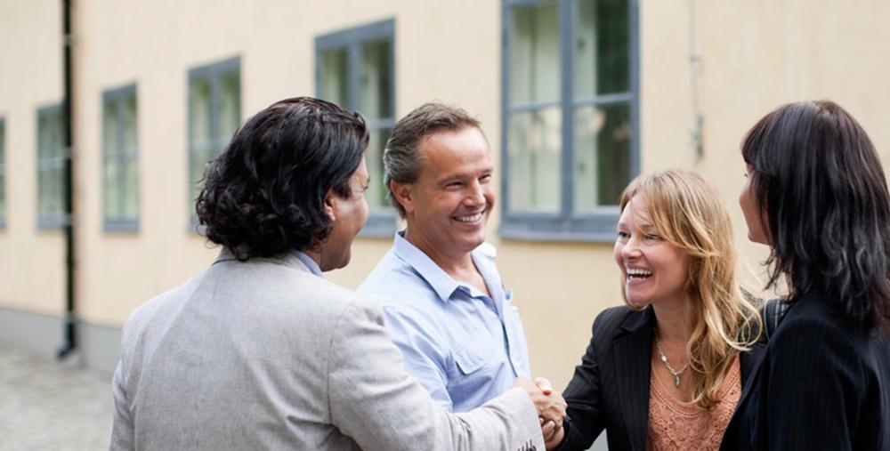 Fire voksne hilser på hverandre. Foto.