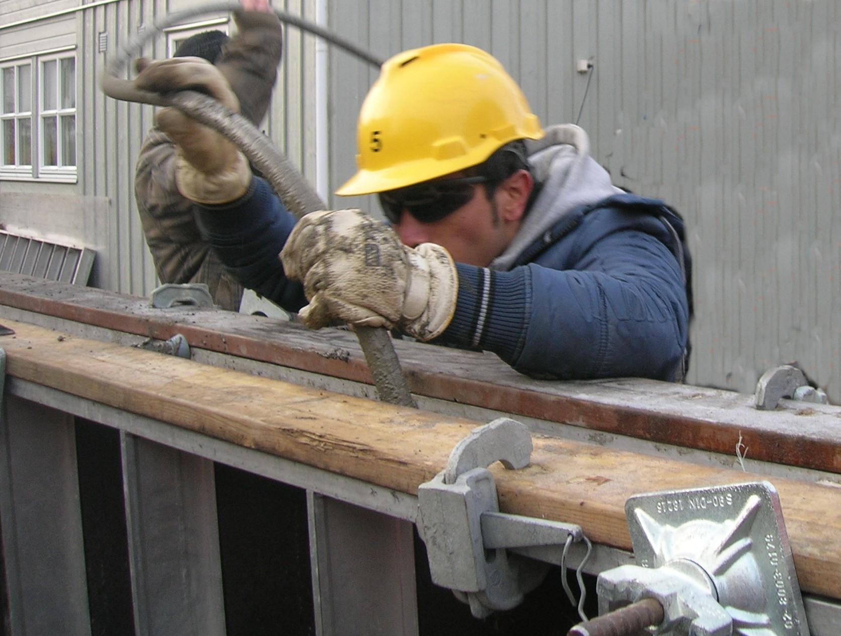 067c9517 Betongarbeider med vernebriller, hjelm og hansker ved støping av betong.  Foto.