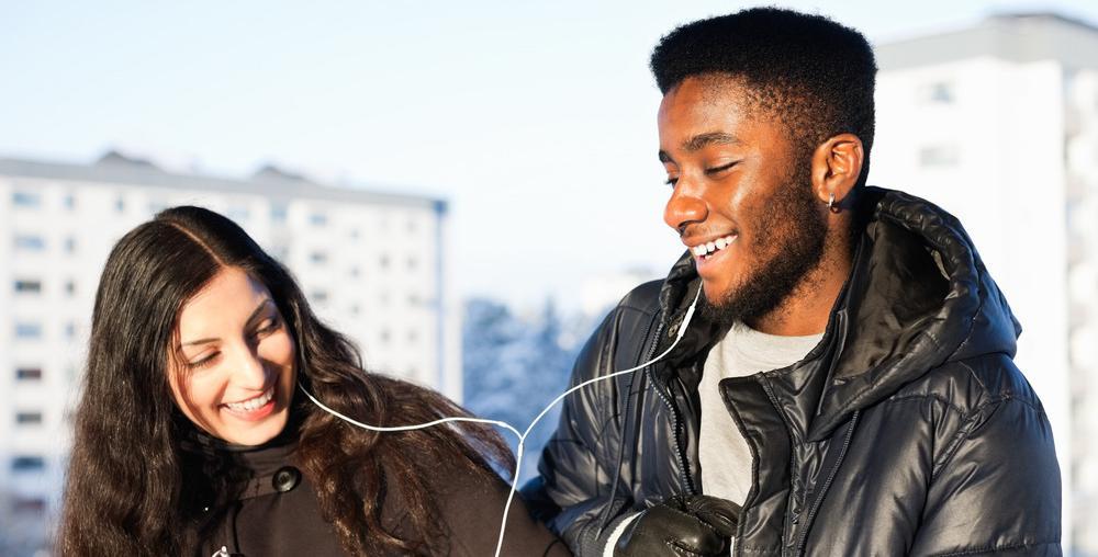 Jente og gutt som hører på musikk fra samme hodetelefoner. Foto.