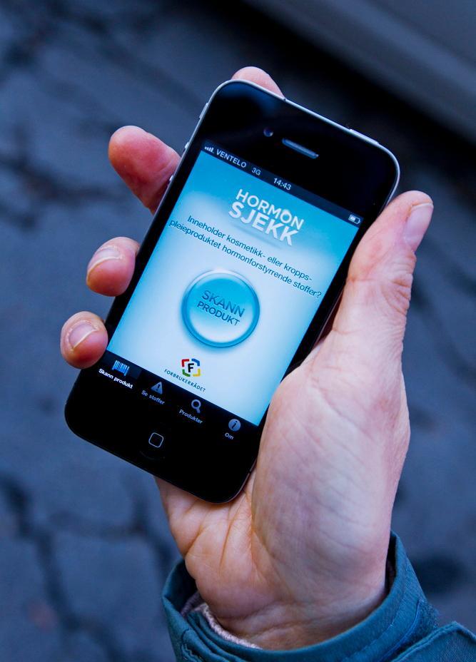 En mann som står med en mobil i hånden og viser frem en app om hormoner.