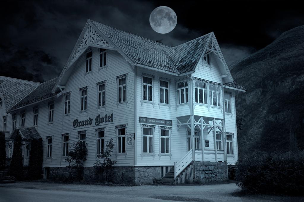 Et gammelt hotell. Hvitmalt trebygning i mørke. Det er natt, men fullmåne. Foto.
