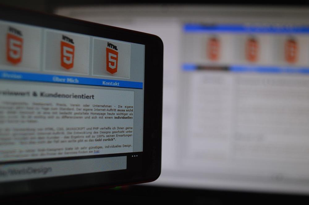 Dataskjerm som viser nettside og html5-logo. Fotografi.