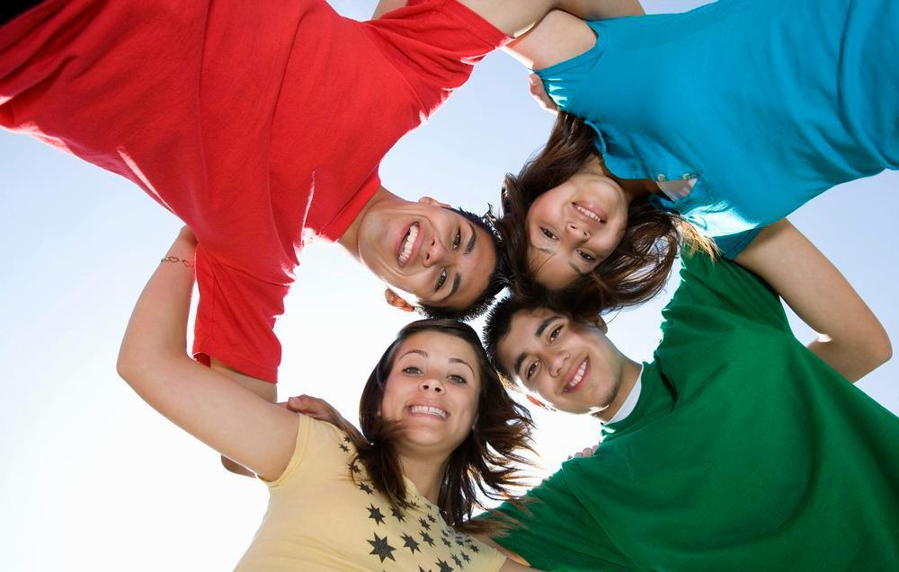 Fire ungdommer holder rundt hverandre og ser ned i kamera.