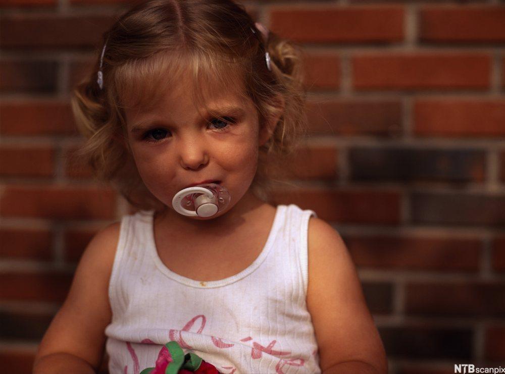 Bilde av ei lita, lyshåra jente med smokk i munnen. Foto.