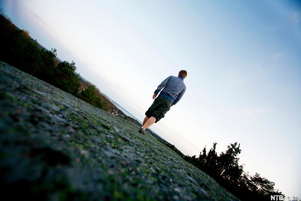 Ung mann på landevei, på vei bort. Foto.