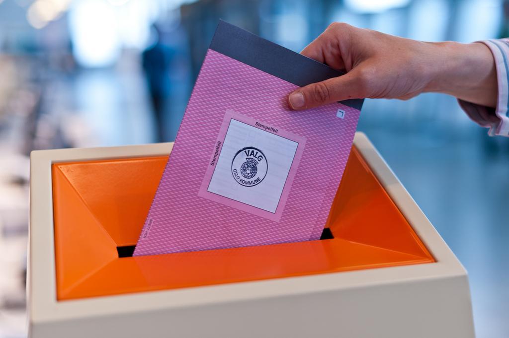 En hånd putter stemmeseddel i valgurne. Foto.