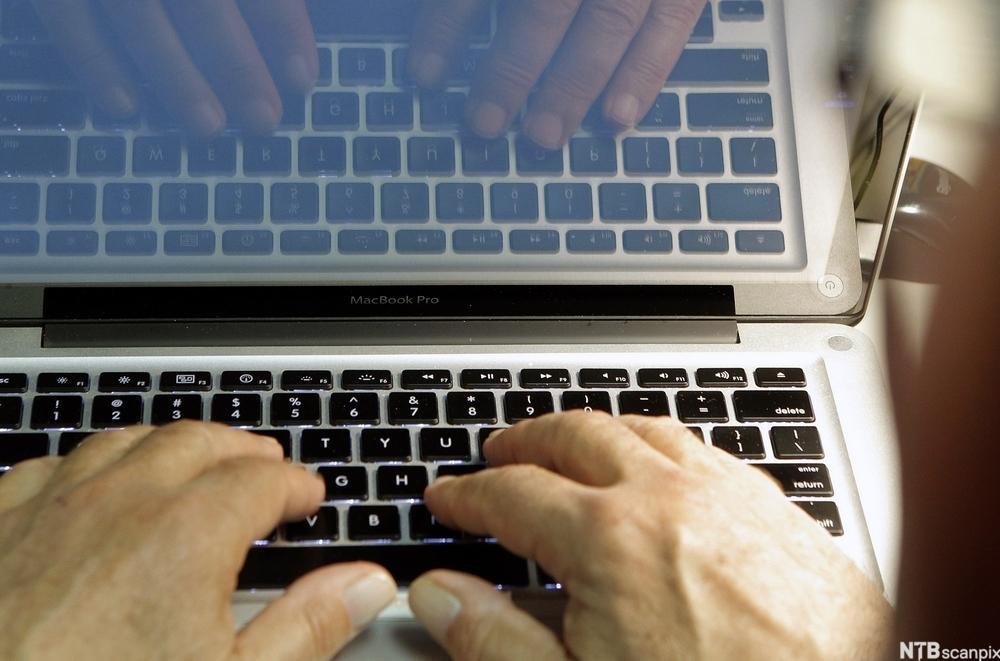 Hender på tastatur.Foto.