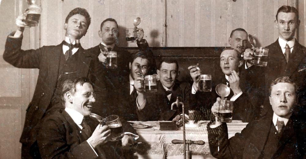 Studenter sitter rundt et bord og reiser en skål med ølglass. Foto.