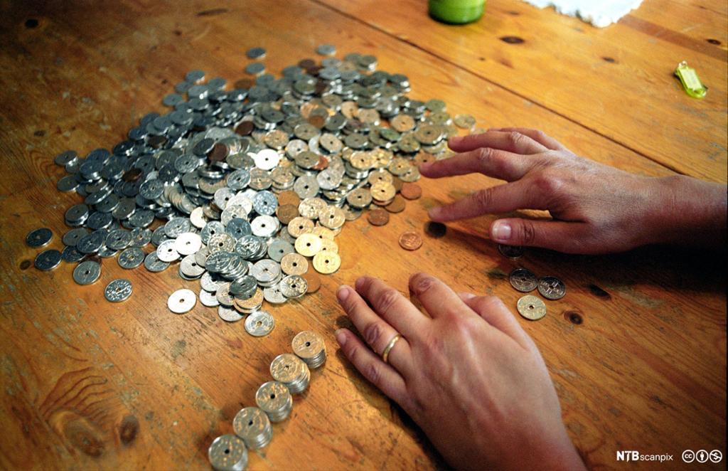 Kvinne teller kronestykker. Foto.