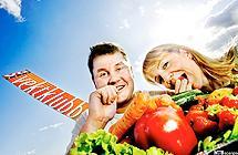 En mann og en kvinne knasker gulrøtter bak en haug grønnsaker, med blå himmel og logoen til VGs Vektklubb i bakgrunnen. Foto.