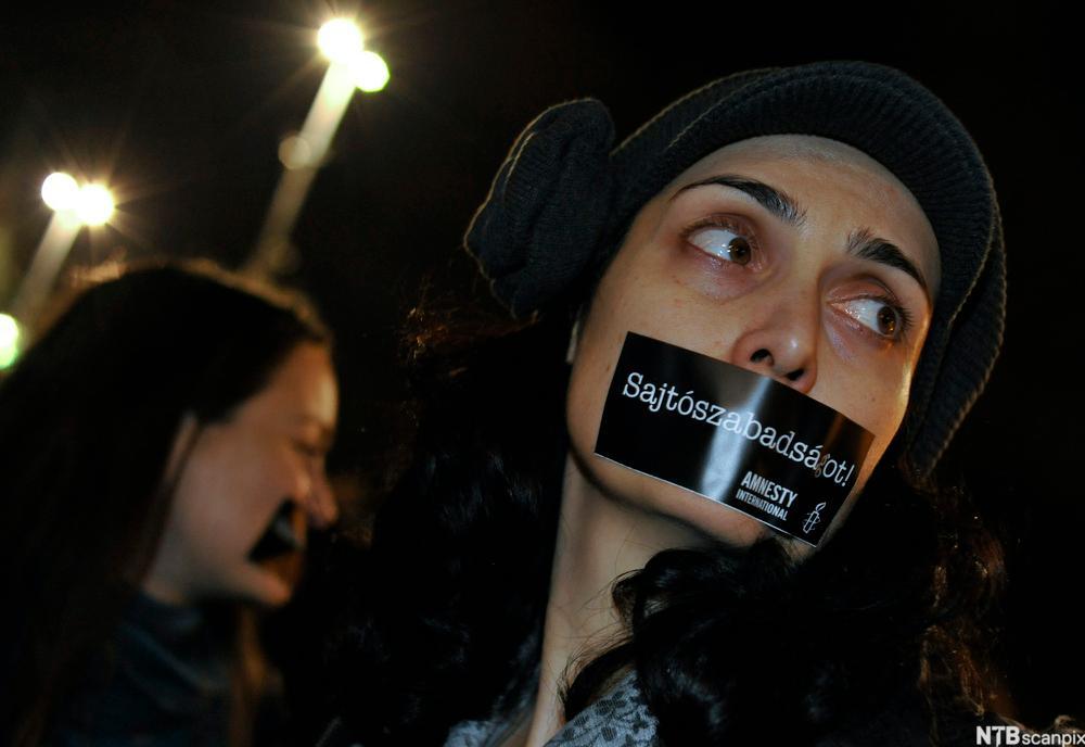 Kvinne med tape over munnen. Foto.