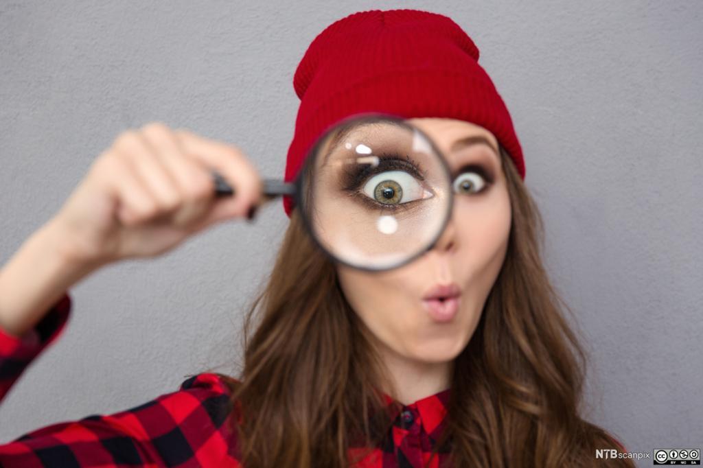 Ung kvinne holder et forstørrelsesglass foran øyet. Foto.