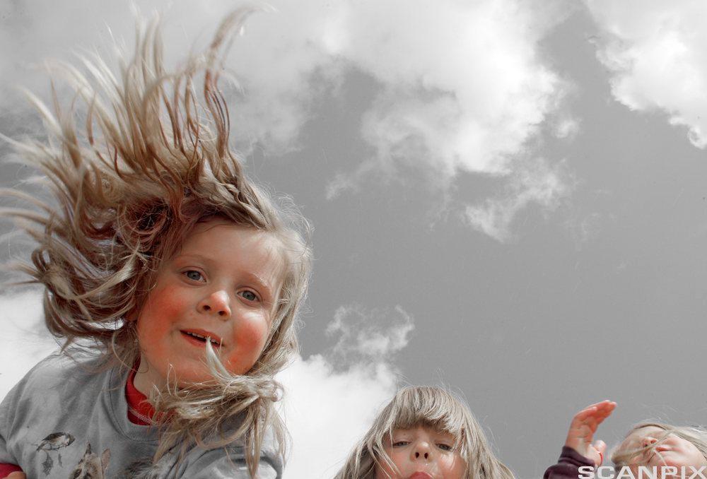 Tre jenter hopper. Foto.
