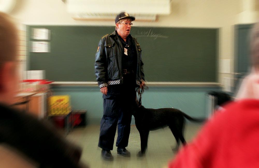 Politi i uniform med hund i klasserom. Foto.