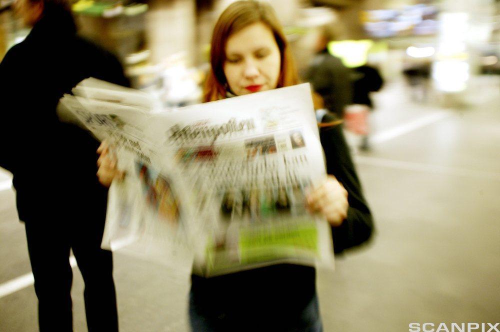 Kvinne leser avisa. Foto.