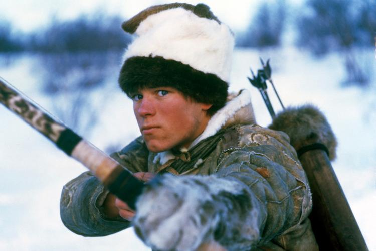 Ung mann med hvit lue og vinterklær står med spent bue og har en sekk med piler på ryggen. Foto.