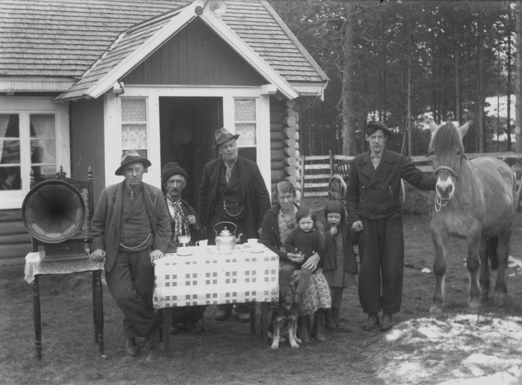 De omreisende, tatere, på Moan i Alvdal. Vi ser en familie med flere generasjoner sittende foran et hus rundt et bord. Den ene mannen holder en hest. Foto.