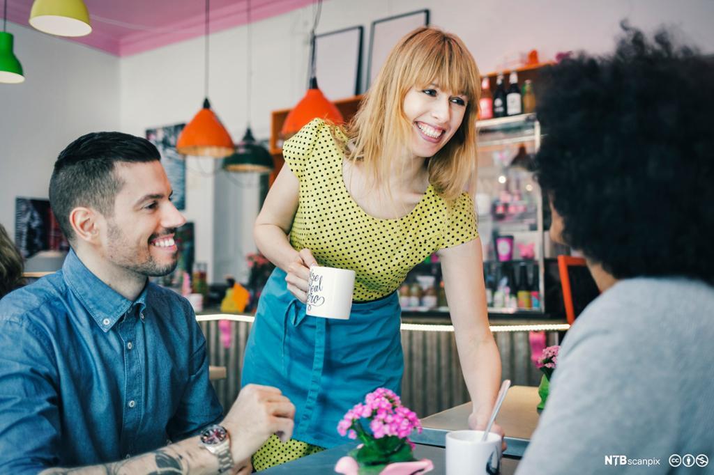 Smilende servitør setter drikke på bordet til to gjester på kafe. foto.