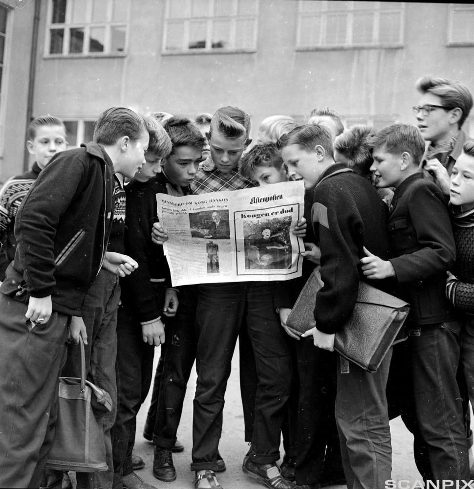 Skolebarn som leser Aftenposten s ekstrautgave i skolegården. Foto.