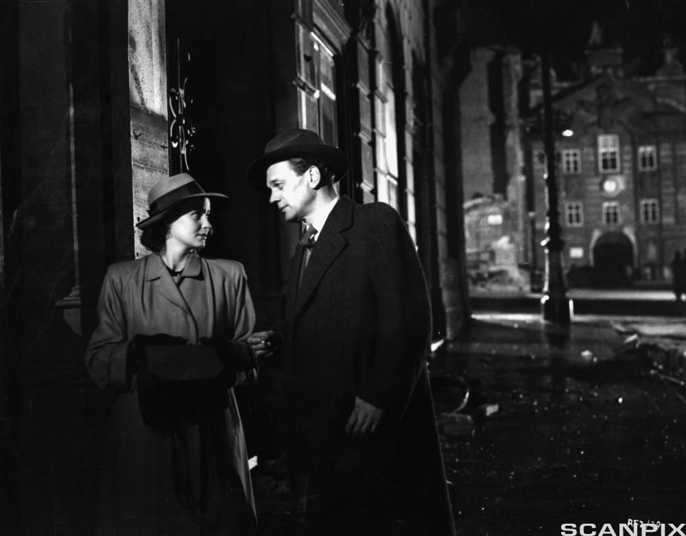 Svart og hvitt bilde av kvinne og mann med hatt og frakk i en mørk gate. Foto.