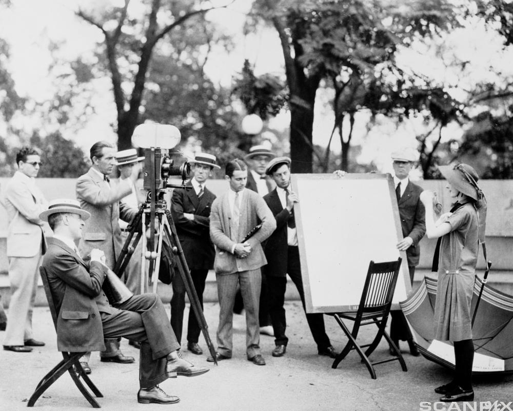 En kvinnelig skuespiller opptrer foran en gruppe menn med filmkamera. Foto.
