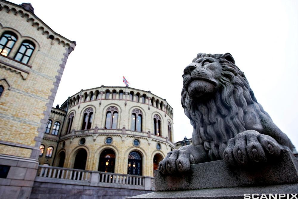 Fasadebilde av Stortinget med løvestatue i forgrunnen. Foto.