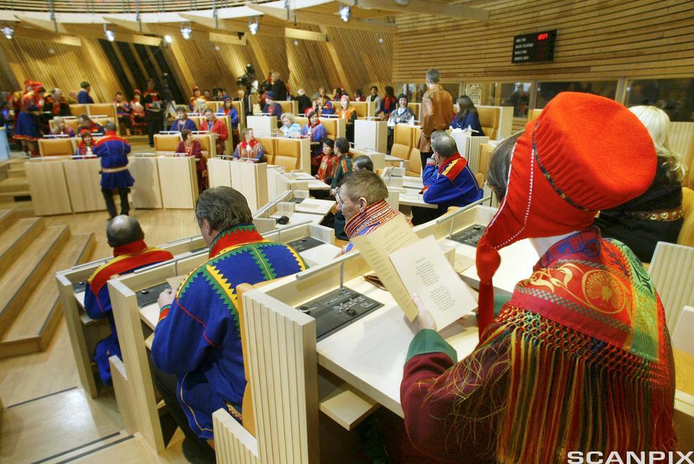 Fra salen i Sametinget. Samer i kofte sitter på plassene sine. Foto.