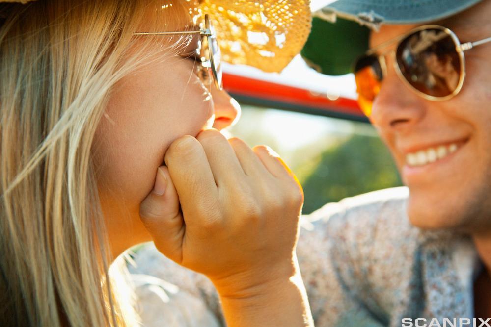 Ung kvinne og ung mann ser på hverandre og smiler. Foto.