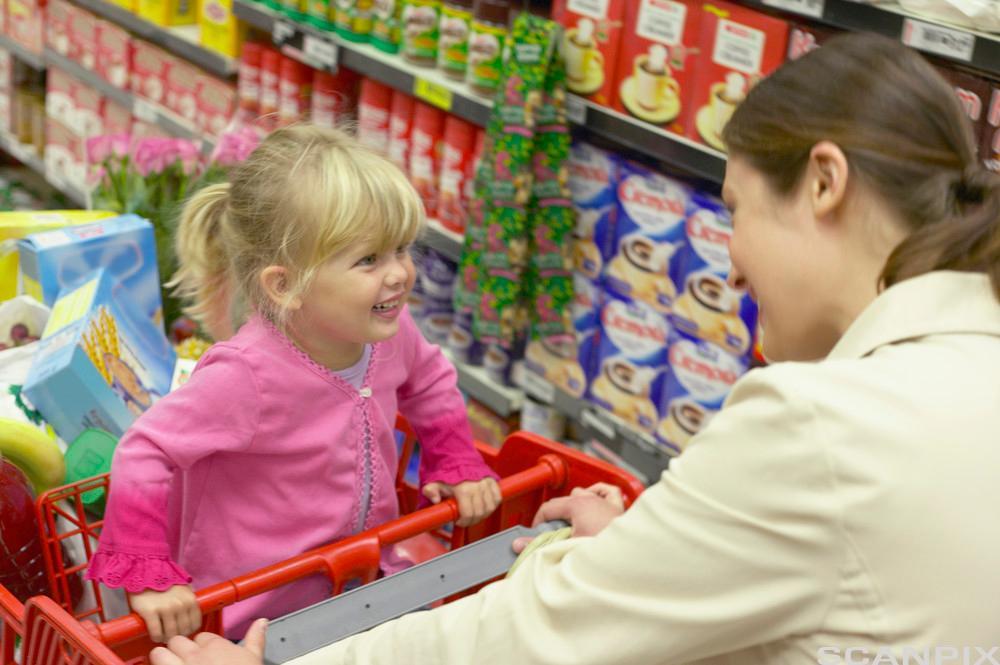 Ei lita jente sitter i ein handlevogn, hun smiler og ser på en dame som står foran henne. Foto.