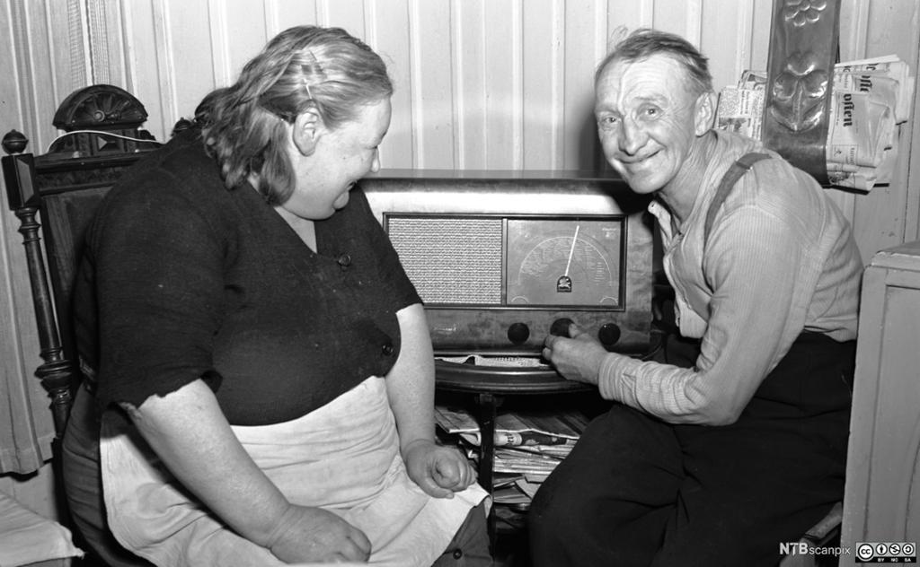 Et eldre ektepar sitter ved radioapparatet og lytter og smiler. Bilde.