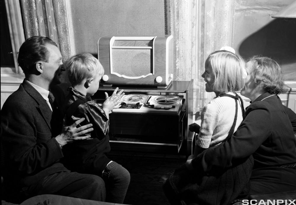 Familie med mor, far og to barn sitter foran radioapparatet i typisk 1950-tallsstue. Foto.