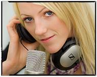 Ung dame med et par øreklokker foran en mikrofon. Foto.