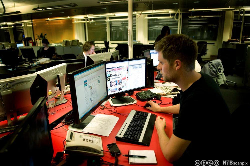 Journalist Mads A. Andersen foran PC-skjerm i VGs redaksjonslokale. Fotografi.
