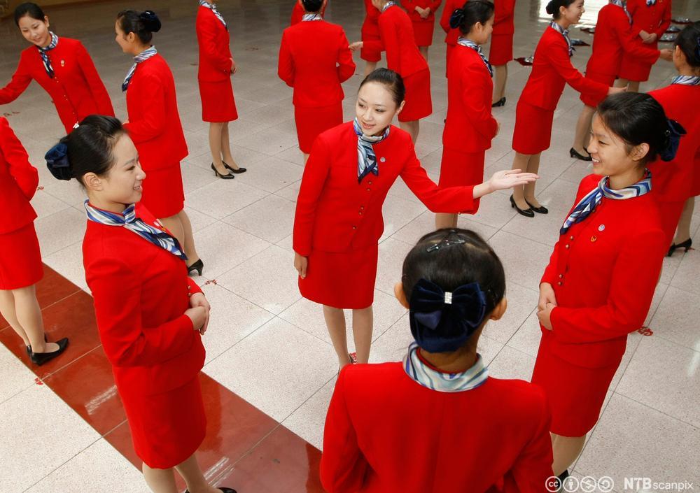 Unge, kvinnelige studenter i røde drakter lærer etikette. Foto.