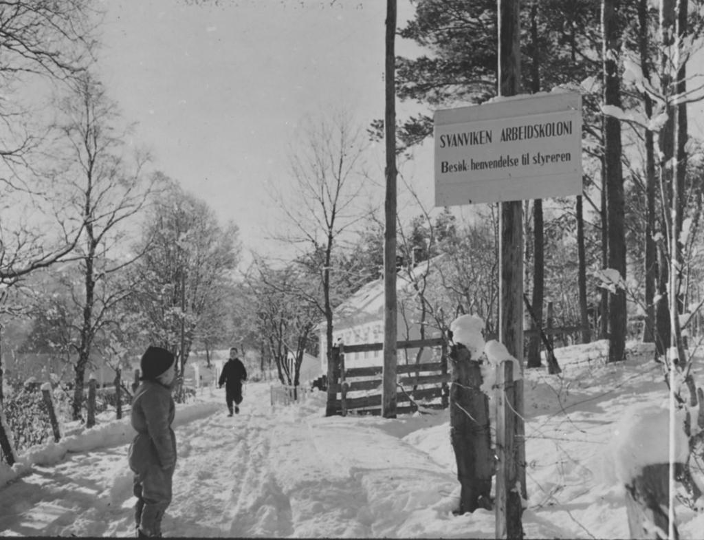 Svanviken arbeidskoloni. Vinterscene med barn i snøen ved innkjørsel til Svanviken med skilt. Foto.
