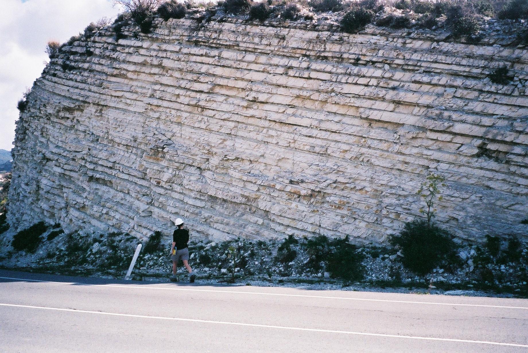Det avkuttede fjellstykket langs veien viser laginndeling i kalkstein. Foto.