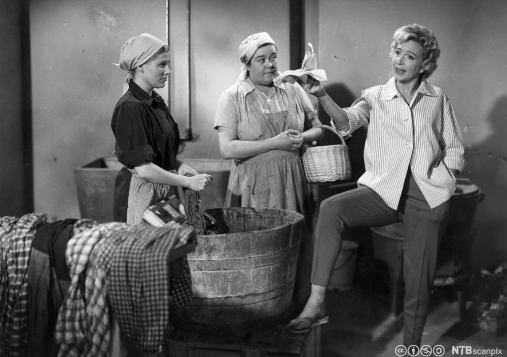 Tre kvinner står og snakker sammen i en vaskekjeller. Foto.