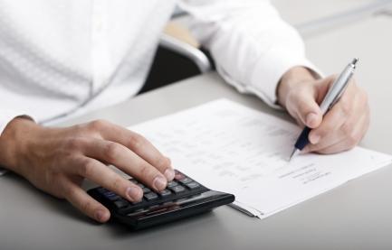 En person holder en kalkulator i ei hånd, og en penn i den andre, med et ark foran seg. Foto.