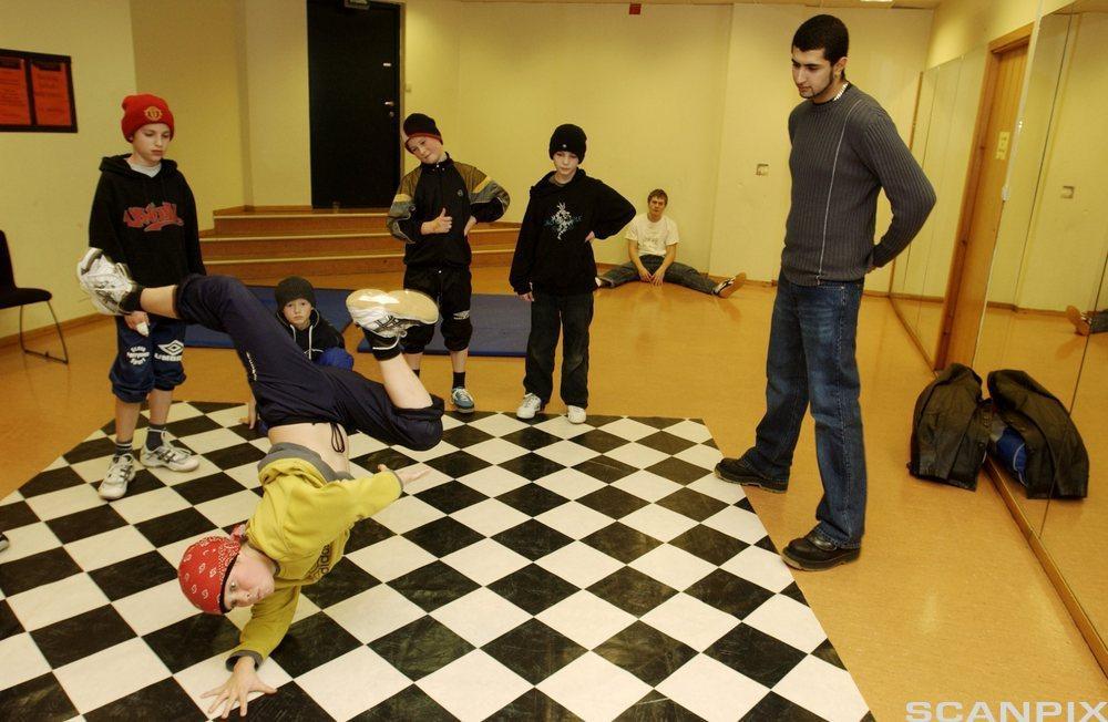 Gruppe med ungdommer, en som danser. foto.