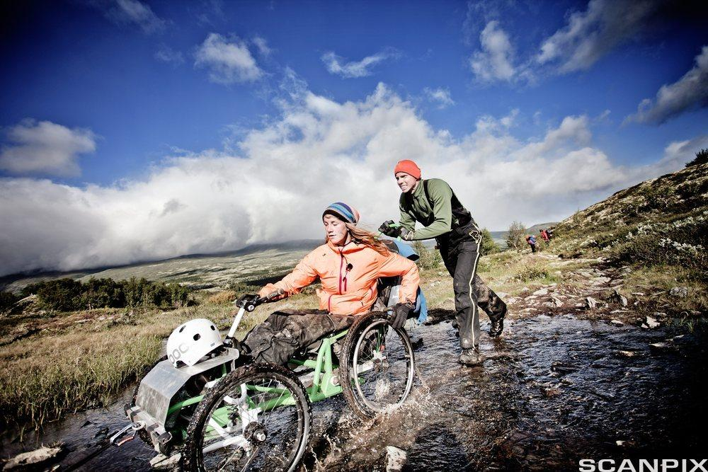 Mann dytter kvinne i rullestol i terreng.Foto.