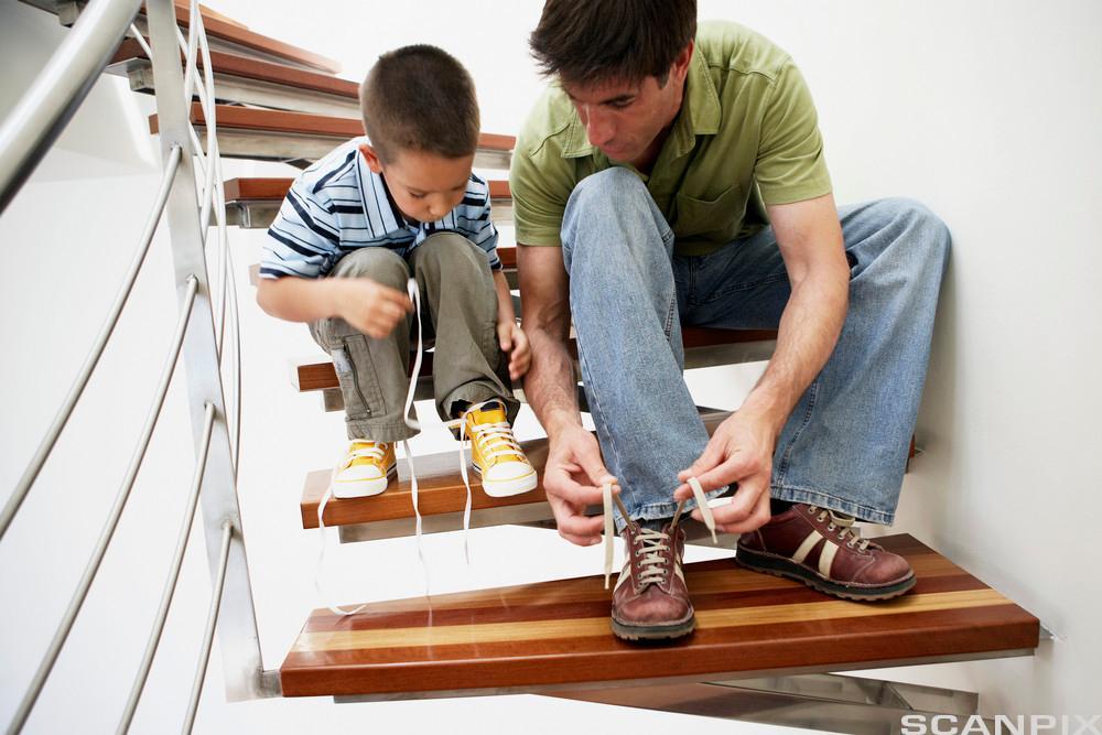 Ein vaksen mann og ein liten gut sit ved sida av kvarandre i ei trapp og knyter skoa sine. Mannen held opp lissene så guten kan sjå kva han gjer. Foto.