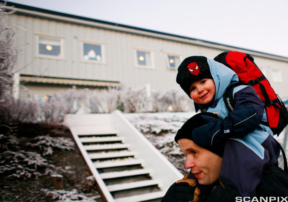 Mann med gutt i bæremeis på ryggen. Foto.