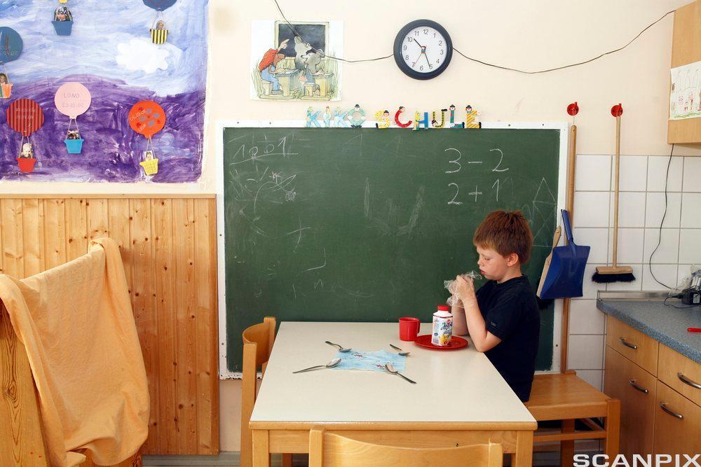 Et barn sitter ved et bord i et klasserom. Foto.