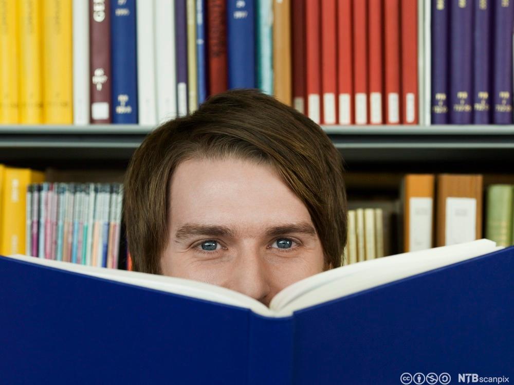 Nærbilde av en ung, smilende mann som gjemmer en del av ansiket bak ei bok. Bokreoler i bakgrunnen. Foto.