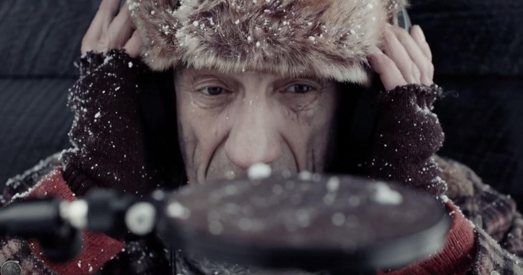 Mann med lue, holder seg for ørene. Filmutsnitt.
