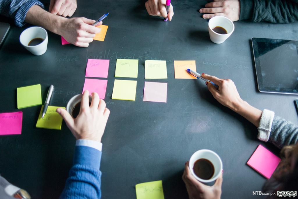 Armer som samarbeider over et bord med post-it lapper. Foto.
