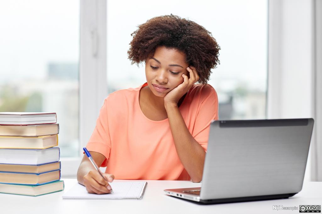 Jente som skriver på ark og PC. Foto.
